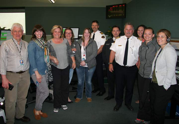 New Westminster Fire Chiefs visit with E-Comm staff in the communication centre during 9-1-1 Awareness Week.