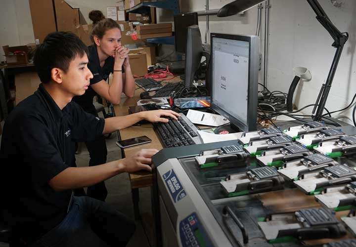 E-Comm wireless technicians engrave new P25 radios in anticipation of agencies transitioning to the new network.