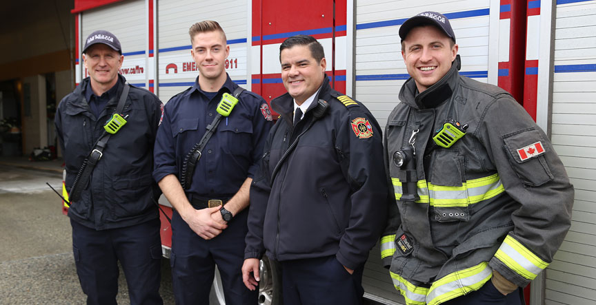Vancouver Fire and Rescue Services Chief Darrel Reid (second from the right) joins firefighters outfitted with new radios.